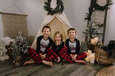 holiday mini session photo shoot christmas pajamas siblings neutral teepee greenery garland candles tree lights ladder reindeer blondes bear buffalo check plaid