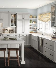 Give your kitchen a fresh update with classic white cabinets. In this space, dark flooring creates a bold contrast.