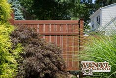 """Grand Illusions Vinyl WoodBond Rosewood (W105) vinyl PVC wood grain fencing shown in a stepped style V500A-6 Semi-Privacy with 1-1/2"""" & 6"""" wide boards."""