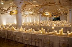 Love the long rectangular tables, the table numbers with driftwood suspended from the ceiling and the mix of chairs.