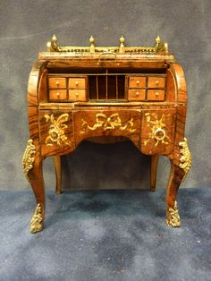 Chris Malcomson - Rosewood Cylinder Desk, circa 1760. Inspired by the David Roentgen desk, this desk is adorned with floral marquetry and drapery much like the original. The legs are tapering cabriole legs with 24ct gold plated ormolu mounts. selling on Lilliputland for $3350