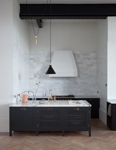 Under-the-counter cupboards from the Plain English Spitalfields line and an island from the Plain English Osea range. An extended backsplash of Carrara marble is paired with white walls and exposed industrial beams. Carrara marble counters and arabescatto marble island worktop.