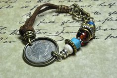 10 Pence UK coin bracelet with glass and howlite beads and bronze & silver color beads.  Suede cord and toggle clasp.