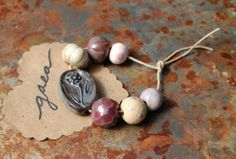 These hand picked, love and gardentone, artisan made ceramic beads are hand formed, hand carved and an original design! This listing is for the items shown in the photo!