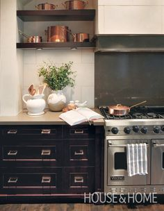 A collection of copper pots on open shelves draws attention to the dramatic stove in this upscale country kitchen designed by Nam Dang-Mitchell. | Photographer: Colin Way