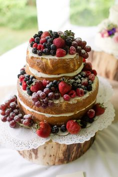 A delicious naked cake topped with rasberries, blackberries, strawberries, blueberries, and red grapes.     Photo by Dan and Melissa Photography