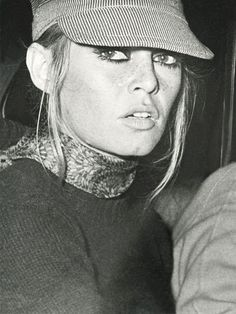 Brigitte Bardot wears a striped fisherman's cap with a scarf and sweater