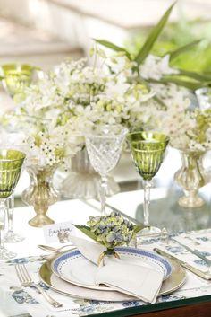 Para compor a mesa, louça Vista Alegre Cozinha da Matisse Casa, jogos americanos florais azul e branco, porta-guardanapo de hortênsia verde e guardanapos em linho verde oliva.