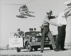 Making an arrest - Los Angeles county Sheriff's Department.  Vintage police car