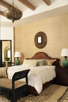 bedroom with grasscloth walls, British tan leather headboard, turquoise lamps & turquoise throw pillow - interior design by Bonesteel Trout Hall