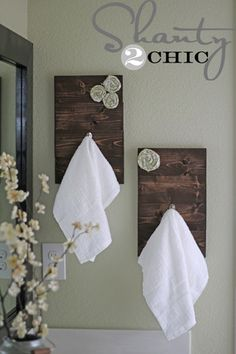 Dark wood towel hooks with fabric rosettes - Decoist