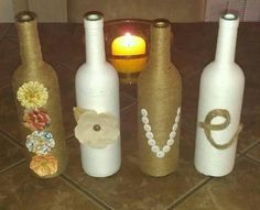 Wine bottles recycled as vases. The best part...emptying the bottles. Used twine and white string yarn to cover bottles using modpodge. Floral embellishments, buttons, and twine for lettering.