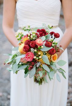 A mixed bouquet made of red and peach mums, yellow ranunculus, white snowberries, and greenery, created by Twigs, Leaves and Flowers.