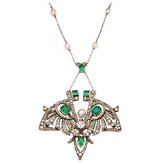 This stunning Art Nouveau pendant necklace features a 1.40 carat mine cut diamond surrounded by two cushion cut emeralds, two pear shaped emeralds and two square step cut emeralds. The stones are set in a silver on 18 karat yellow gold hand wrought and assembled mounting.