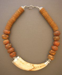 Anna Holland / Dorje Designs - Mottled brown ceramic beads and very old vulcanite heishi from Africa with a wild boar tusk found in South Africa Chunky Jewelry, Tribal Jewelry, Statement Jewelry, Beaded Jewelry, Handmade Jewelry, Jewelry Necklaces, Beaded Necklace, Unique Jewelry, Yoga Jewelry