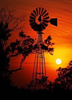 Could be the ending of a beautiful evening with the setting of the sun in the background and the statuesque windmill in the foreground. I miss our windmill. The sound it used to make as it went round and round in the wind. :)  Those were the days my friends!