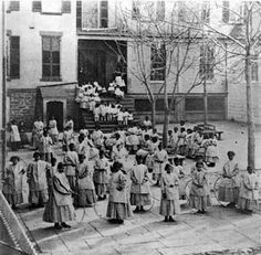 1861 photo of girls in the school yard of the Colored Orphan Asylum, located at 5th Ave. & 43rd St. in New York City.