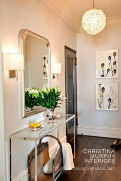 traditional elements like the French mirror mixes well with modern touches .....the Lucite console, abstract paintings, and capiz flower hanging pendant.