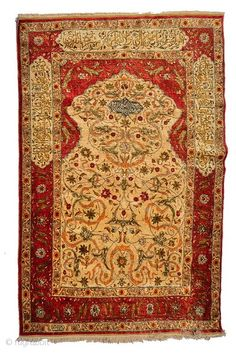 A TURKISH, HEREKE SILK RUG, the central camel ground panel with inscription and scrolling foliate design within a deep red border, further inscribed, 183 x 121cm To be auctioned on Wednesday 3rd June ...
