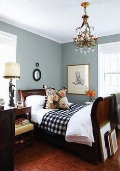 Blue- grey, dark wood, white trim. Love the touch of orange in cushion and flowers. Design by Tommy Smythe
