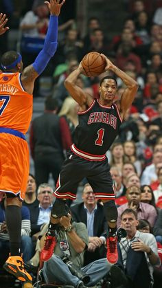 CHICAGO, IL - OCTOBER 31: Derrick Rose #1 of the Chicago Bulls keeps the ball from going out of bounds and passes over Carmelo Anthony #7 of the New York Knicks at the United Center on October 31, 2013 in Chicago, Illinois.