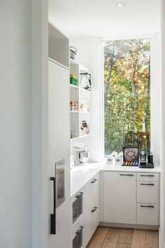 An Attractive Storage Room With White Built In Storage And Modern Cabinet With Glass Window And Wooden Flooring A Large Three Storey House Exhibits Modern Luxury Home design