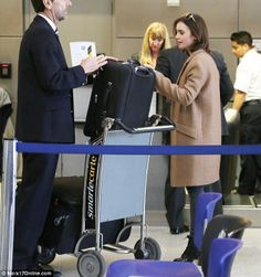 She'll be In the Air Tonight: Lily Collins is the anti-diva as she queues to hand over her own luggage at LAX   airport style: brown aviators, oversized camel Zara coat, burgundy jumper, gray skinny jeans, black crocodile skin tote bag (not real i hope) & black heeled lace-up boots   Feb. 12, 2014