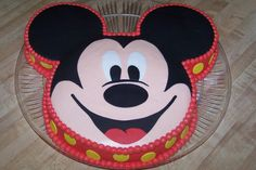 """mickey mouse - This was done with a 10"""" round for the face plus 2 6"""" round for the ears.  Covered in buttercream and fondant accents - ears, nose, eyes, mouth, and polka-dots.  I had trouble with my red...I need to switch coloring brands....I am still using Wilton and it separates easy.  I have heard Americolor is awesome.  Wished I would of made this a double layer but it is still a lot of cake.  I did not plan well for the board and At 10 at night with kids in bed and no husband I was…"""