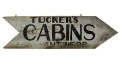 1940s one-sided and hand-lettered arrow-shaped sign for Tucker's Cabins from Antwerp, Ohio. Sign has eye hooks for hanging.