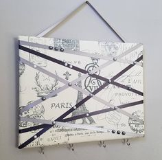 This romantic memo board in natural off-white with grey Paris themed script is accented with asymmetricaly positioned grey ribbon, faux pearls and embellishments. Use it to display your notes, mementos and photos, hair bows etc. Hooks attached to the bottom can hold keys, jewelry and