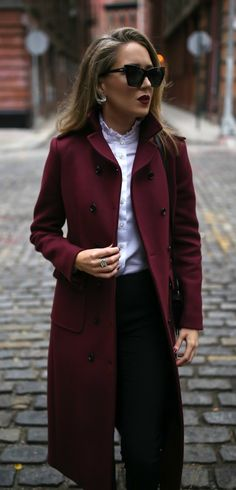 Long burgundy double-breasted coat, metallic silver ankle strap pump, tailored high-waisted black pants, white ruffle blouse, black shoulder bag, deep red lip { Saint Laurent, Valentino, Theory, winter style, what to wear to work, holiday outfits, casual business attire, classic style}