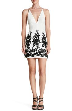 Short and sweet! This mini dress is designed with floral patterns of sequins circling the skirt for a light-catching effect.