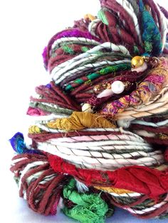 https://flic.kr/p/Qo9Eau   Handspun Art Yarn - Sacred Land   Hand Spun, One of a Kind, 100 % Merino Art Yarn. Gorgeous and embellished goodness! Featuring multicolored beaded embellishment throughout and array of sari silk thread inclusions . Would look fabulous added into a knitting or crochet project or as an inclusion in free form weaving. A stunning 'one time' unique piece. 135 yards / 123 m 35cm 4.8 oz / 138 gm Approx. 10 wpi - (depending on thick/thin spin and embellishments).