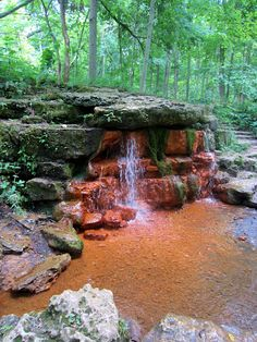 Red waterfall among green trees at Glen Helen Nature Preserve in Yellowsprings, Ohio.