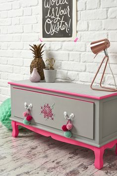 @ Mollie Makes:  Grey & neon pink bench with cross-stitch rose & pompoms