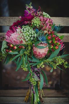 A richly colored bouquet of proteas, thistles, rose hips, Queen Anne's lace, and seeded eucalyptus