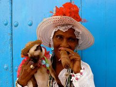 """A colorful Havana woman enjoys an enormous cigar. The smokes are one of Cuba's defining symbols—""""Havanas"""" are renowned worldwide and have special cache among many aficionados in America, where their import remains illegal."""
