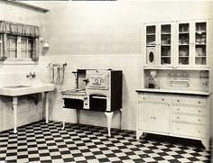 1920 Kitchen. floors and walls were off white, butter yellow ceramic tile, outlined in black. In the center of the kitchen was a big cooks table with butcher block and marble. Not much counter space, walk in pantry and a breakfast nook wrapped in windows.