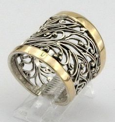 Stunning NEW silver & gold ring. The ring is made of sterling silver with two polished 9k Yellow Gold bars over 20 mm wide very rich pattern filigree band . Enjoy it forever! Labeled&stamped 925. This beauty will be sent to you in a gift package. (All stains, if are any, are due to camera). Please feel free to contact us at any matter.   Material: Sterling Silver 925 925    Dimensions: Front width: 20 mm / 0.787 in., Back width: 14mm / 0.551 in. Size: 7 (and can be resized at your request)…