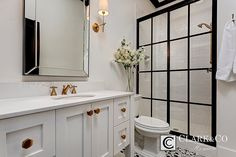 Black panes in walk in shower with brass hardware and fixtures