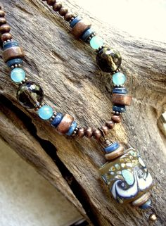 see om inspirations jewelry on FB.  necklace, approximately 16 1/2 inches long, large glass pendant, shell disc beads, blue dyed jade beads, smoky quartz beads, round wood beads, cylinder-shaped beads, small glass beads, antique copper spacer beads, antique copper toggle clasp, $32 includes shipping within the U.S. Feel free to send questions to me via facebook email. To order, send payment via paypal: yoginidb@yogafromthegroundup.com