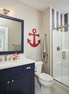 Nautical bathroom in navy and white with red anchor wall decor...