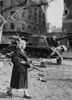 Budapest.1956. A young woman with a rifle in hands on background of two ISU-152.