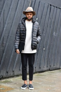 ASOS Kieron wears a black puffa jacket over a white scuba top with a black wallet, black cropped trousers, black slip on trainers and a beige fedora #fashion #style #inspiration #mens