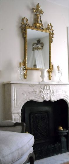 white french fireplace surround with gold mirror