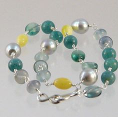 Necklace with grey freshwater pearls, fluorite, amber and green quartz on fine silver with handforged clasp.
