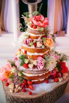 naked wedding cake filled with strawberries, raspberries and fresh cream, decorated with shortbread hearts and flowers