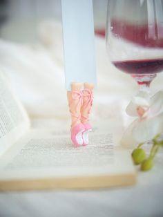 Marcador de la bailarina. Marcador de libro rosado tierno en los zapatos de pointe. Piernas en el libro.