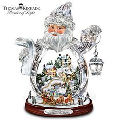 Thomas Kinkade Crystal 3D Santa Claus Figurine. Exclusive first! Sparkling Santa figurine holds a glowing lantern, with 3D village inside. Miniature sleigh and reindeer circle a wood-toned base. #DeckTheHalls