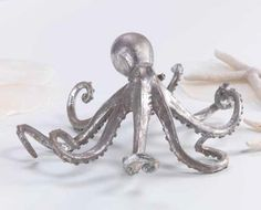 Octopus Accent. Our cleverly rendered Octopus creates a seaside accent for tabletops. Created in an antiqued silver metal for a washed ashore appearance. The unique elevated design and generous size creates a statement piece for your tabletop or mantel.